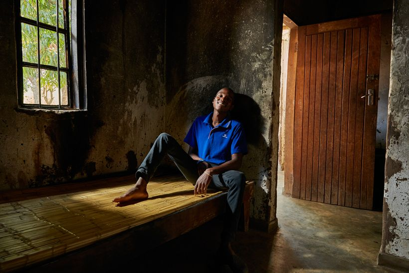 Alex (19) sits in the bedroom of his gowelo that was damaged by a recent fire, Thyolo District, Malawi, 2016.  After the pare