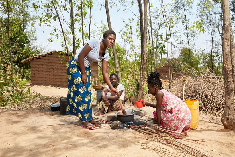 Sisters Gertrude (16), Elisa (14) and Maureen (11) cook in the courtyard of their gowelo, Thyolo District, Malawi, 2016.