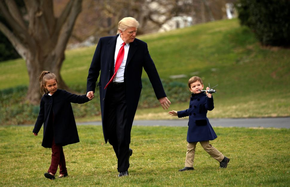 Joseph Kushner holds up a toy Marine One as his grandfather, Donald Trump, holds hands with him and his sister Arabella as th