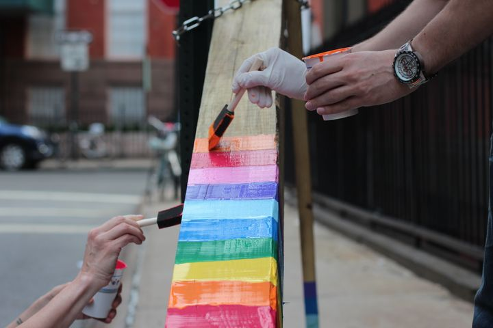 Gay St. residents painting a cross that appeared on their block.