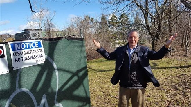 Bart Mitchell, who coordinates affordable housing projects in Boston, gestures to an empty lot where a new project is to be b