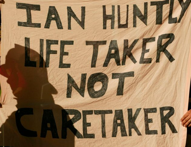 Protesters hold up a banner as Ian Huntley arrived at court to face murder charges in