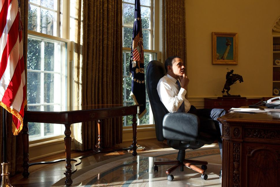 Obama sits in the Oval Office on his first day in office, Jan. 21, 2009.