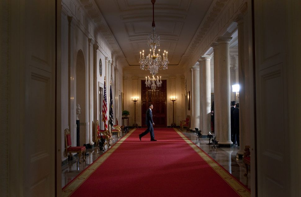 Obama walks to a podium in the Cross Hall, Grand Foyer of the White House, before making a statement regarding the American a