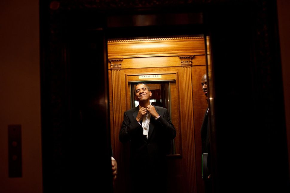 Obama rides the elevator to the private residence of the White House after attending 10 inaugural balls and being sworn in as
