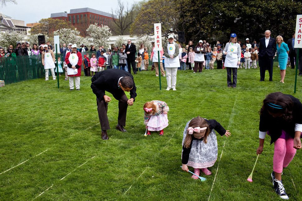 Obama cheers on a young child as she rolls her egg toward the finish line April 13, 2009, during the White House Easter Egg R