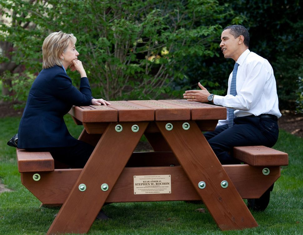 Obama and Secretary of State Hillary Clinton speak together sitting at a picnic table on April 9, 2009, on the South Lawn of