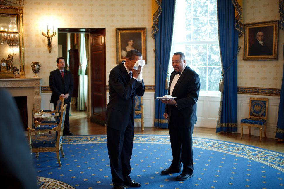 Obama wipes his face with a cloth handed to him by White House butler Von Everett in the Blue Room of the White House followi