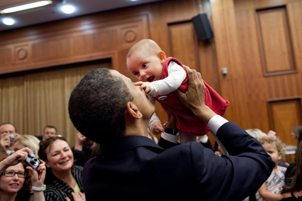 Obama lifts up a baby on April 4, 2009, during the U.S. Embassy greeting at a Prague hotel.