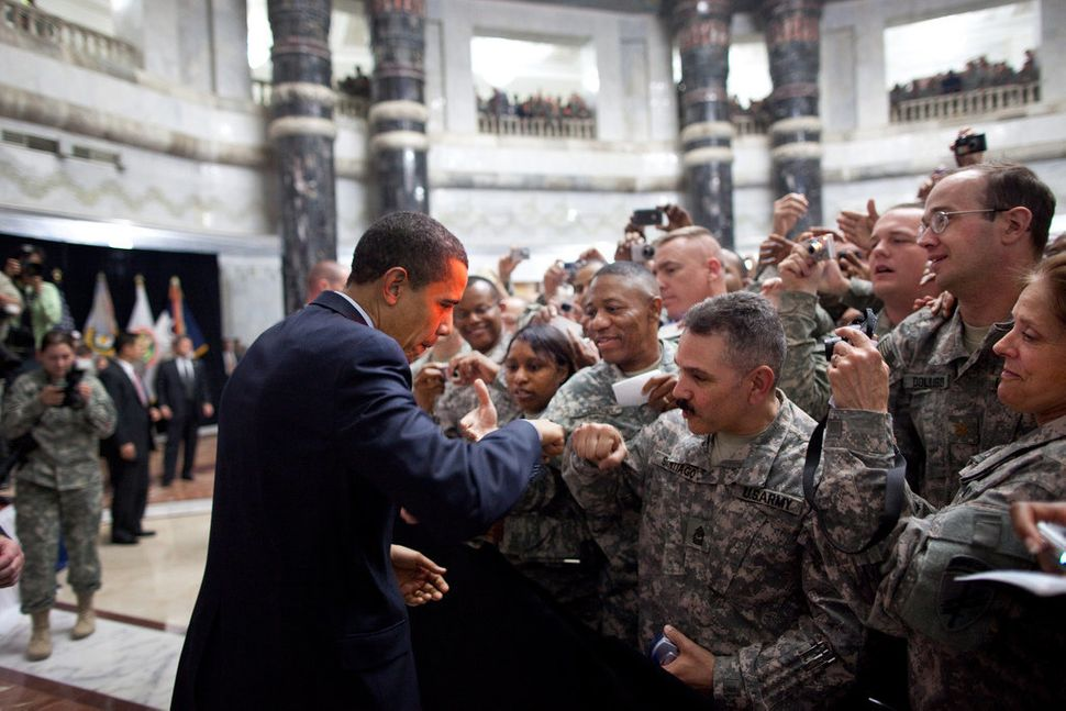 Obama receives a fist-bump from a U.S. soldier as he greets hundreds of U.S. troops during his visit to Camp Victory, Iraq, o