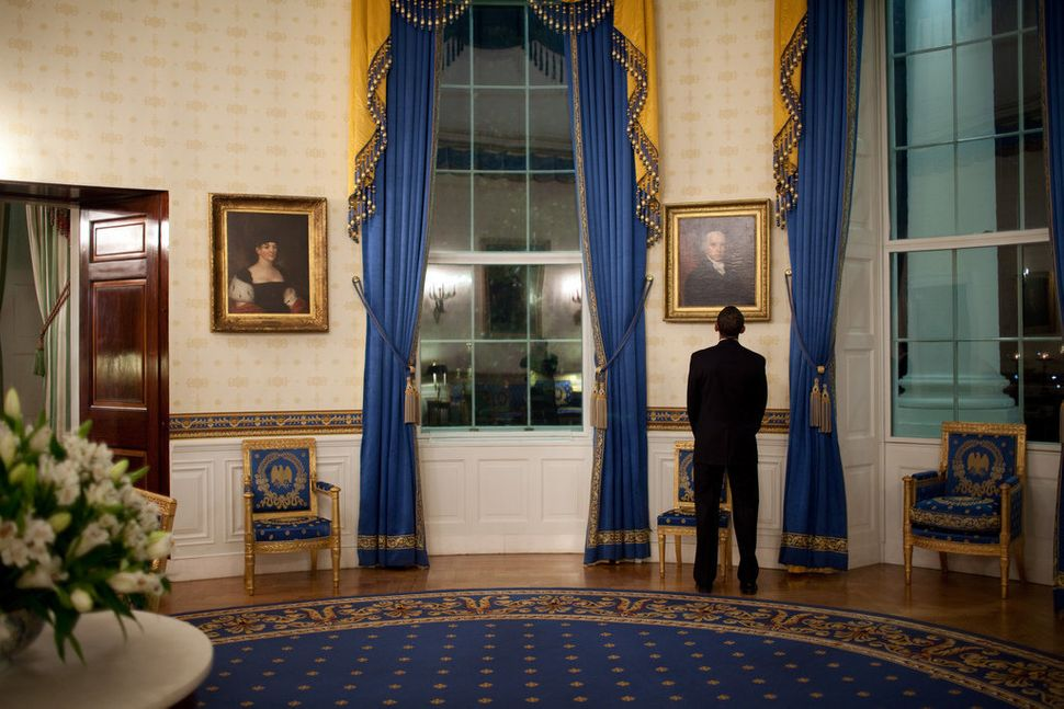 Obama looks at a portrait of President James Madison while waiting in the Blue Room of the White House before his press