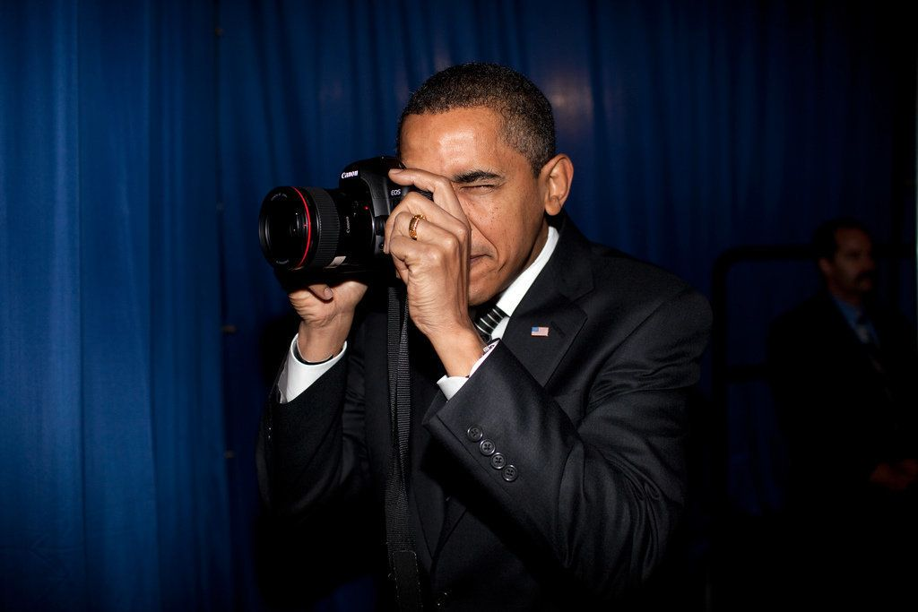 President Barack Obama takes aim with a photographer's camera backstage prior to giving remarks about providing mortgage paym