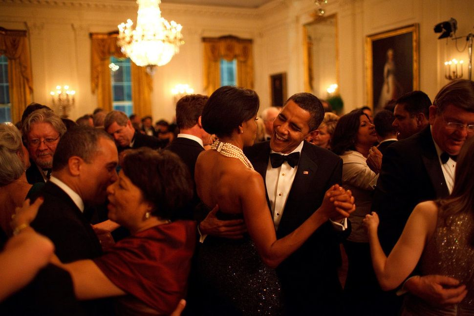 Obama and the first lady dance while the band Earth, Wind and Fire performs at the Governors Ball in the East Room of th