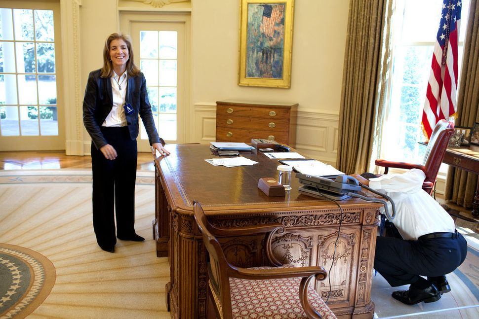Obama examines the Resolute Desk on March 3, 2009, while visiting with Caroline Kennedy Schlossberg in the Oval Office. In a