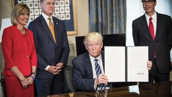 U.S. President Donald Trump, center, displays a signed directive on tax and Wall Street regulations as Steven Mnuchin, U.S. Treasury secretary, right, Representative Claudia Tenney, a Republican from New York, left, and Senator David Perdue, a Republican from Georgia, stand in Washington, D.C., U.S., on Friday, April 21, 2017. The tax code became too expensive and burdensome under former President Barack Obama's administration, making a review of 2016 and 2017 tax rules necessary, Mnuchin said. Photographer: Pete Marovich/Bloomberg via Getty Images