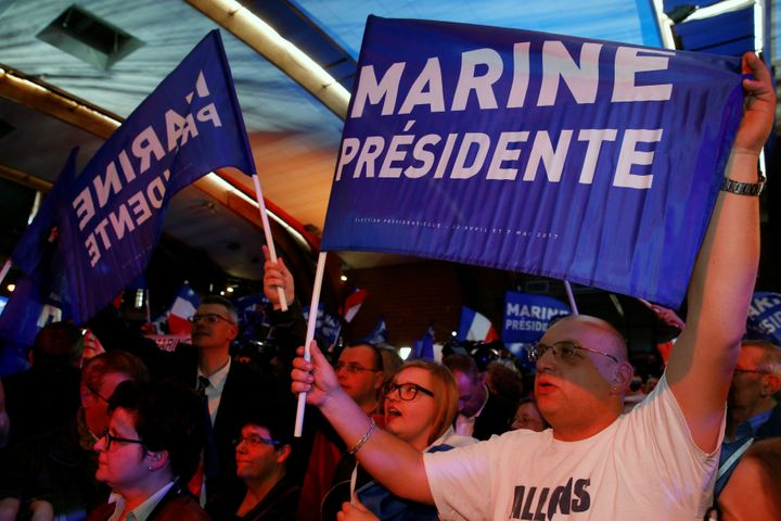 Supporters of Marine Le Pen hold flags as they wait for her arrival in Henin-Beaumont.