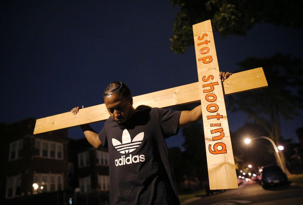 A protester takes part in a weekly nighttime peace march through the streets of a South Side Chicago neighborhood on Septembe