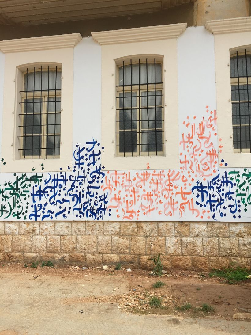 """Arabic calligraphy on the walls of Basmeh & Zeitoonah reads """"Love; Peace; Honesty."""""""