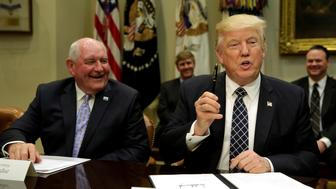 U.S. President Donald Trump holds a pen after signing an executive order next to Secretary of Agriculture Sonny Perdue during a roundtable discussion with farmers at the White House in Washington, U.S. April 25, 2017. REUTERS/Yuri Gripas