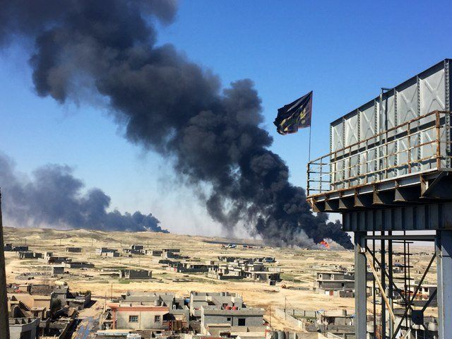 Smoke rises above Qayyarah displacement camp in March 2017.