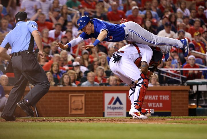 Toronto Blue Jays' Chris Coghlan scores by leaping over St. Louis Cardinals catcher Yadier Molina in the seventh inning.