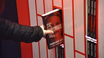 NEW YORK, NY - APRIL 26:  A guest interacts with an art installation, designed by Paula Scher and Abbott Miller, and book giveaway celebrating Hulu's 'The Handmaid's Tale' opens on the High Line on April 26, 2017 in New York City.  (Photo by Bryan Bedder/Getty Images for Hulu)