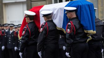 French police officers carry the flag-draped coffin during a ceremony honouring the policeman killed by a jihadist in an attack on the Champs Elysees, on April 25, 2017 at the Paris prefecture building. French police officer Xavier Jugele was killed on the world-famous Paris avenue on April 20, in an attack claimed by the Islamic State group. (Photo by Julien Mattia/NurPhoto via Getty Images)