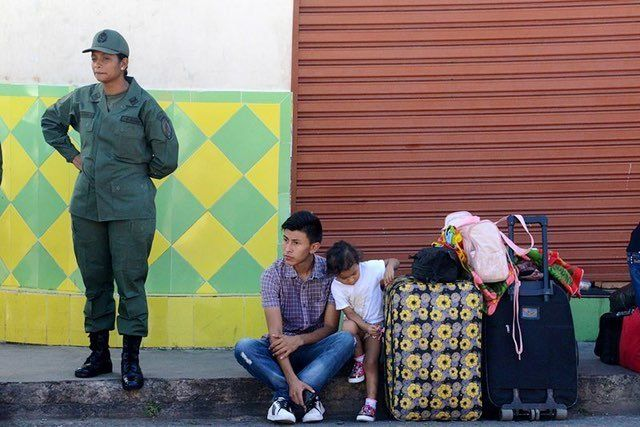 People wait outside the customs office in San Antonio del Tachira, Venezuela, for the opening of the passage to the Simon Bol
