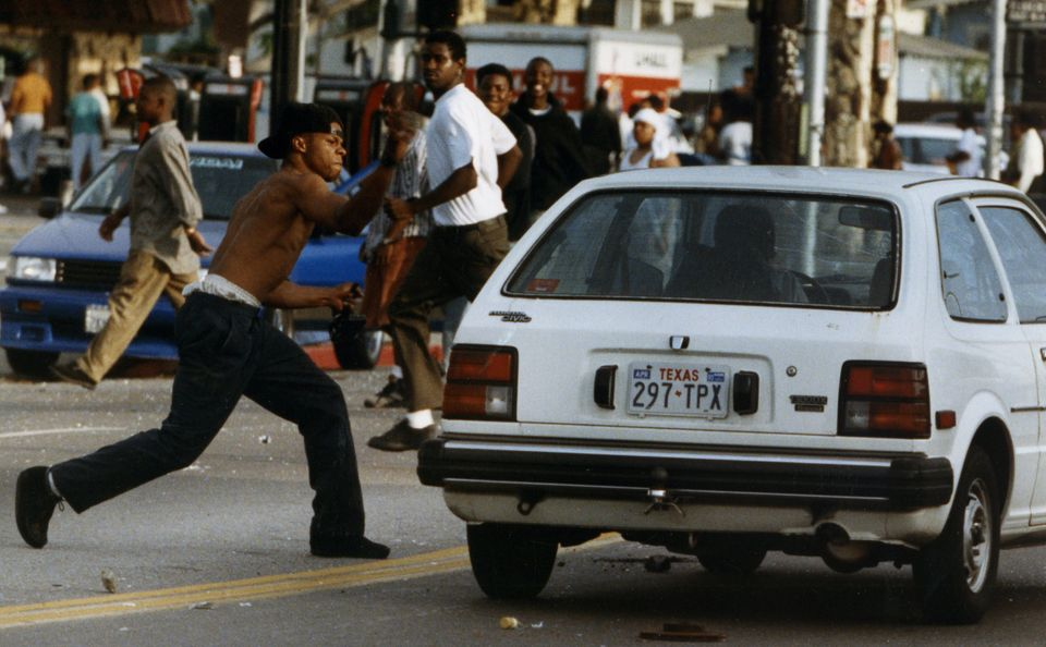 A rioter attacks a car on Florence and Normandie in Los Angeles on April 29, 1992.