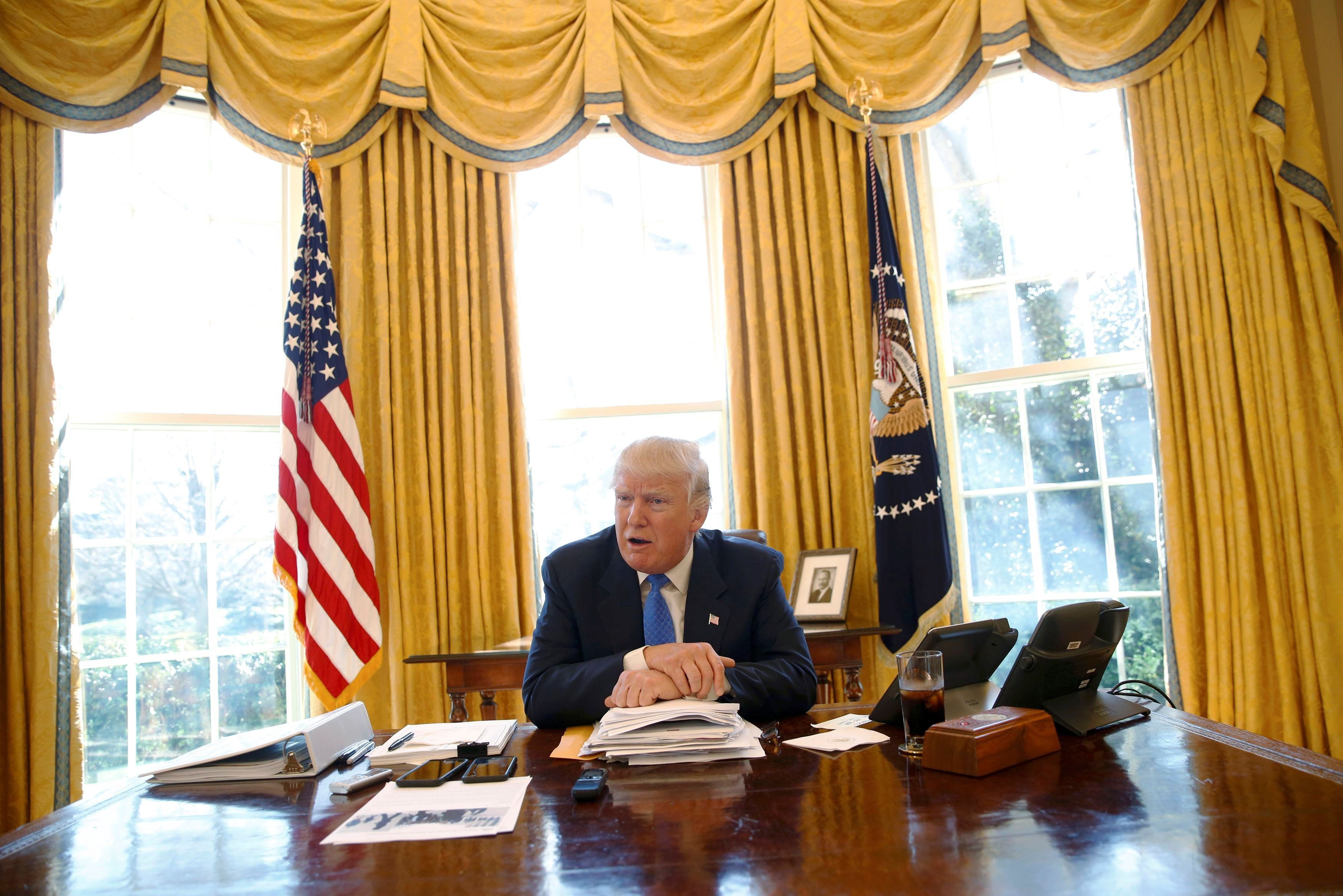 Trump sits at his desk in the White House's Oval Office during an interview in February. An iced...