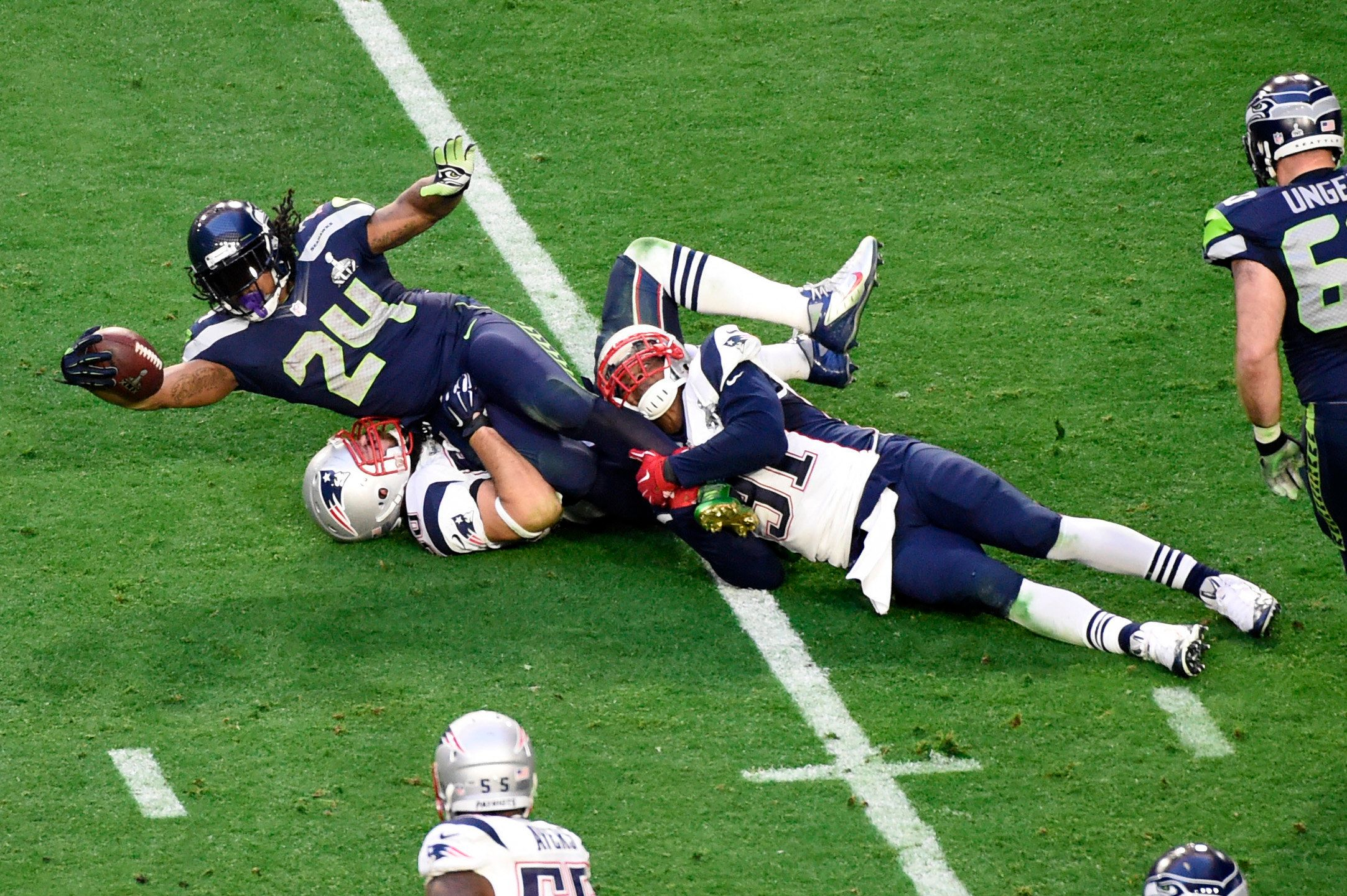 Feb 1, 2015; Glendale, AZ, USA; Seattle Seahawks running back Marshawn Lynch (24) runs the ball against New England Patriots defensive end Rob Ninkovich (50) and New England Patriots outside linebacker Jamie Collins (91) in Super Bowl XLIX at University of Phoenix Stadium. Mandatory Credit: Richard Mackson-USA TODAY Sports