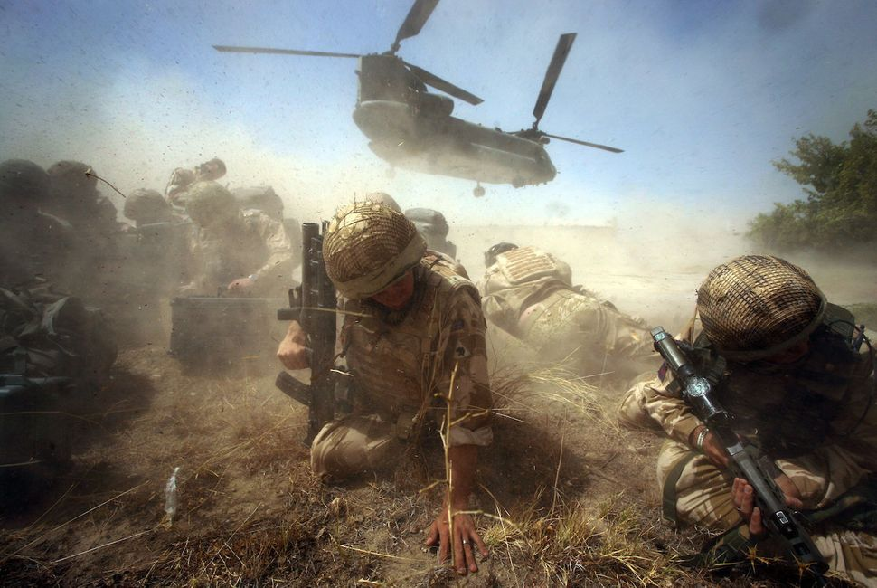 British army troops shelter from the dust storm as their chinook helicopter departs from Cher-E-Anjir town in Helmand Provinc