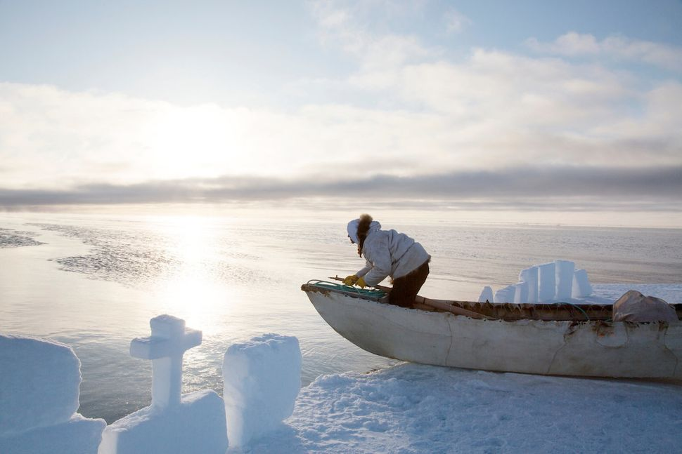 Iñupiat harpooner Quincy Adams surveys the horizon in a sealskin canoe for bowhead whales, miles from the Alaskan town