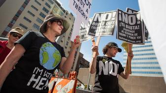 Nicki Thibeault, right, hands out Refusefascism.com signs for the March for Science Los Angeles in Los Angeles, California April 22, 2017. REUTERS/Kyle Grillot