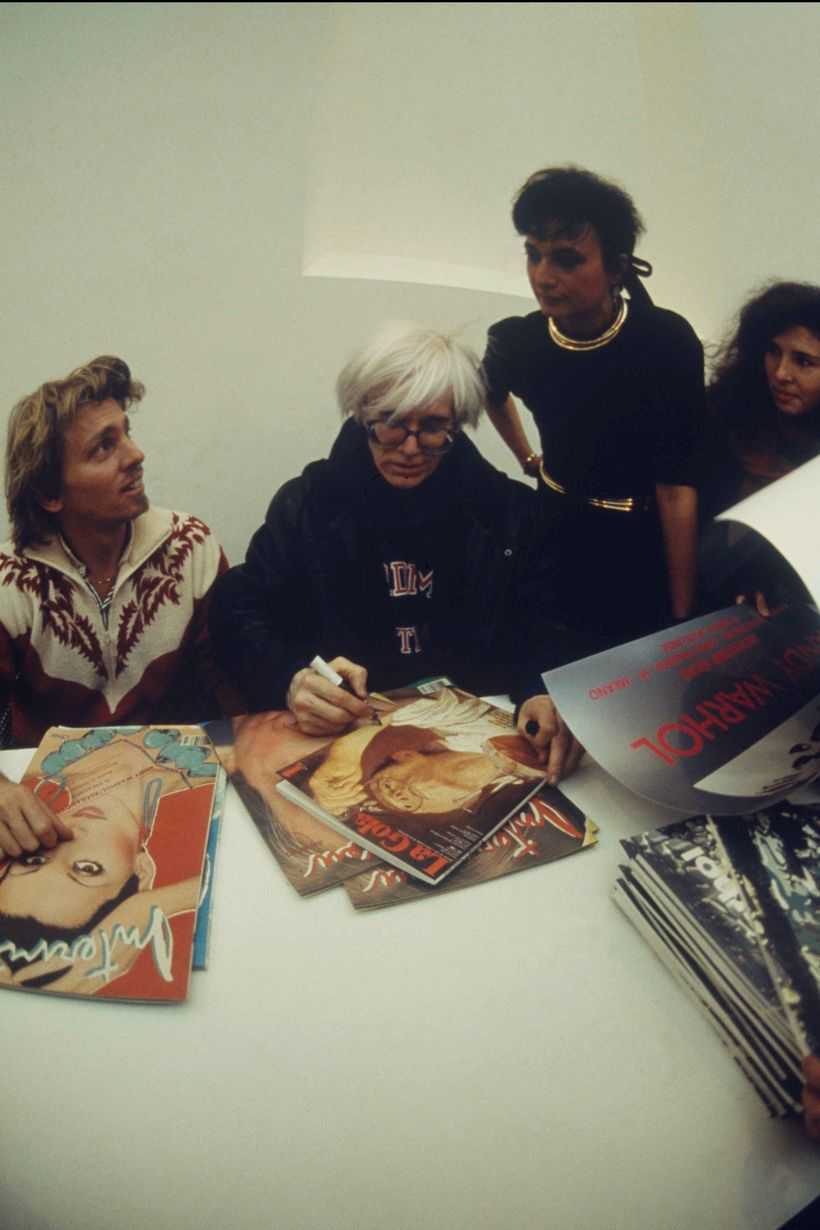 At the historic opening: Andy Warhol,flanked by Christopher Makos and Daniela Morera,  signing autographs away. .