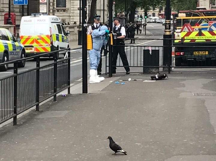 This picture showsat least two knives on the ground and a forensic officer collating evidence shortly after the incident