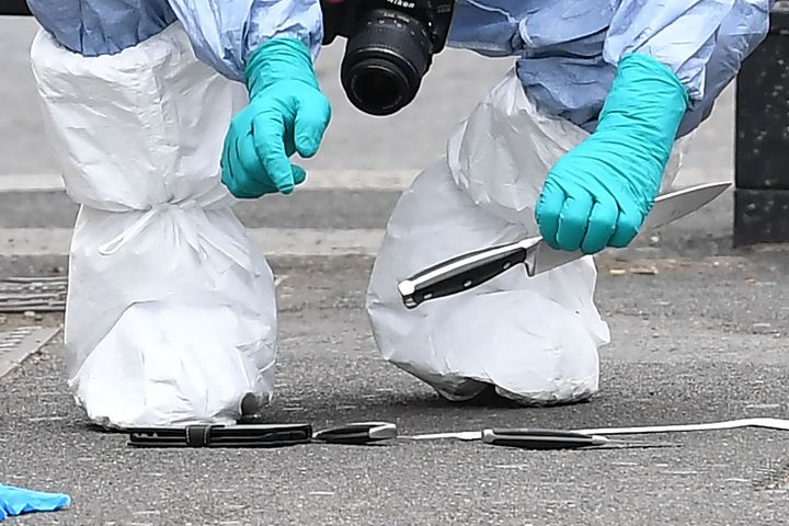 A forensic officer holds up a largeknife among items left on the ground after an incident on Whitehall
