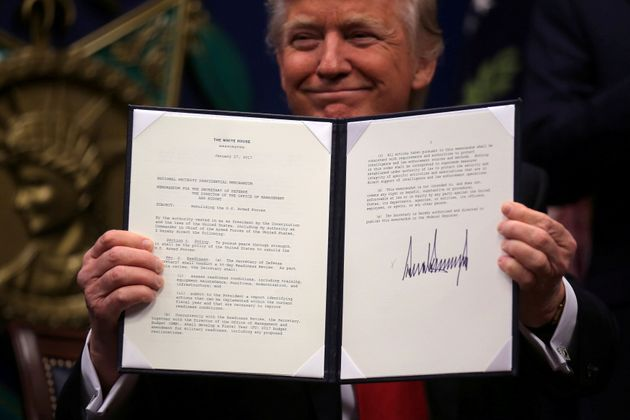 President Donald Trump shows off an executive action after signing it at the Pentagon on Jan. 27. He...