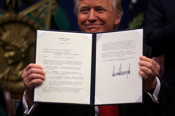 President Donald Trump shows off an executive action after signing it at the Pentagon on Jan. 27. He said this order would be
