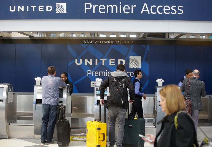 Travelers check in at a United Airlines counter at O'Hare International Airport in Chicago. The violent removal of a doc