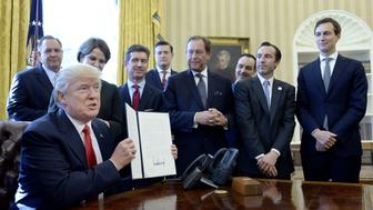 U.S. President Donald Trump holds up a signed executive order as business leaders stand in the Oval Office of the White House in Washington, D.C., U.S., on Friday, Feb. 24, 2017. Trump signed an executive order to impose additional oversight on government regulations, designating officials within government agencies who will monitor rule-making and identify needed policy changes, he said. Photographer: Olivier Douliery/Pool via Bloomberg