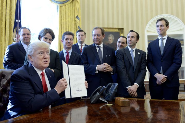 President Donald Trump holds up a signed executive order as business leaders stand in the Oval Office on Feb. 24, 2017. Food