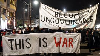 Protesters march with signs in Berkeley, California on February 1, 2017. Violent protests erupted on February 1 at the University of California at Berkeley over the scheduled appearance of a controversial editor of the conservative news website Breitbart. / AFP / Josh Edelson        (Photo credit should read JOSH EDELSON/AFP/Getty Images)