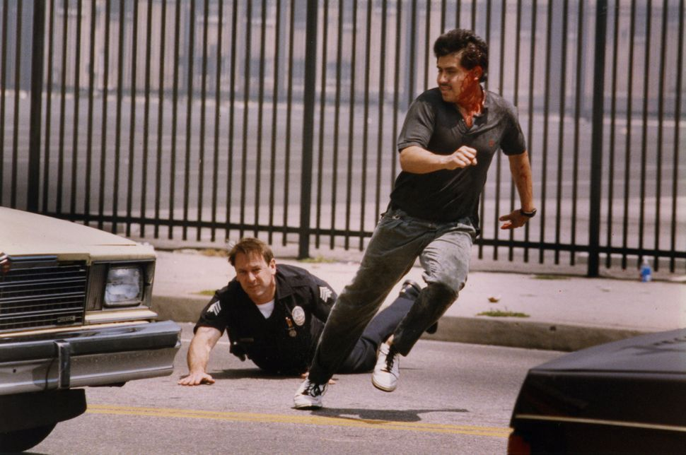 An LAPD officer falls while chasing a suspected looter on Vermont near Martin Luther King Jr. Boulevard on April 30, 1992.