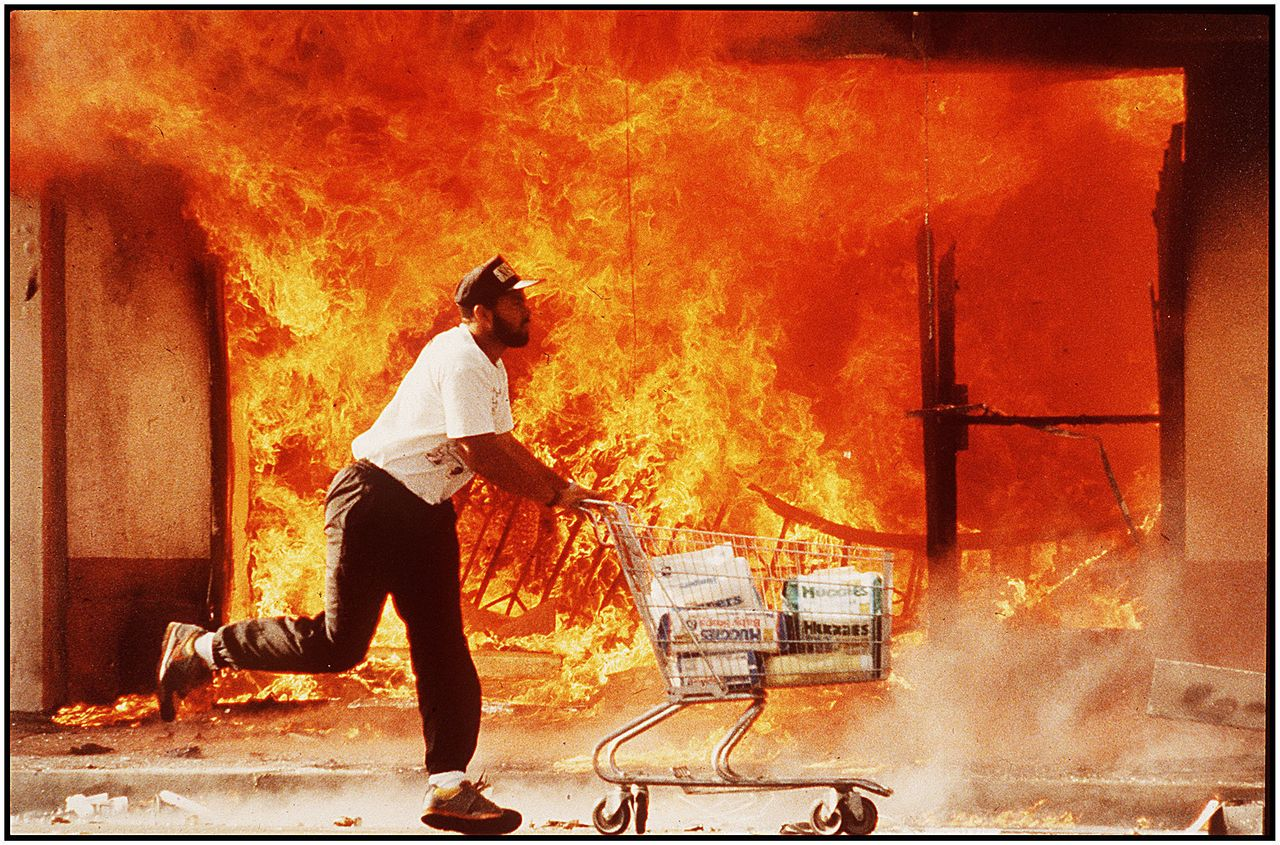 """""""The second day of the riots on 3rd street, I photographed this guy running past a burning Jon's market with a shopping cart full of diapers. I affectionately call this image 'A Huggies Run,'"""" says Kirk McKoy, who took this photo on April 30, 1992."""