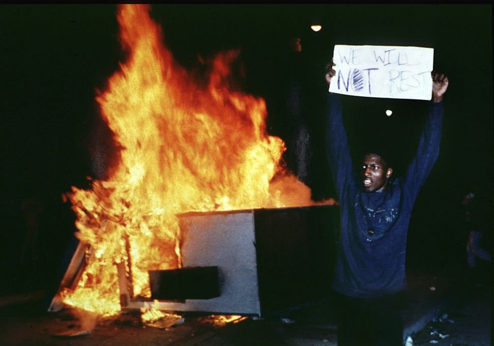 A man holds up a sign at Los Angeles City Hall to protest the Rodney King verdicts on April 29, 1992.