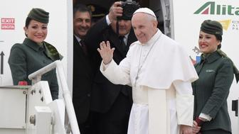 Pope Francis waves from the gateway as he is welcomed by Alitalia's hostesses before to board a plane to Egypt, on April 28, 2017 at Rome's Fiumicino airport . Pope Francis is heading for a two-day visit in Egypt for talks with the grand imam of the capital's famed Al-Azhar mosque in Cairo, but also to show solidarity with Coptic Christians targeted by violence in Egypt. / AFP PHOTO / Tiziana FABI        (Photo credit should read TIZIANA FABI/AFP/Getty Images)