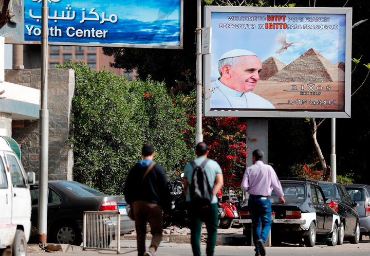 Egyptians walk past a billboard depicting Pope Francis, a few hours before his visit commences on April 28, 2017.