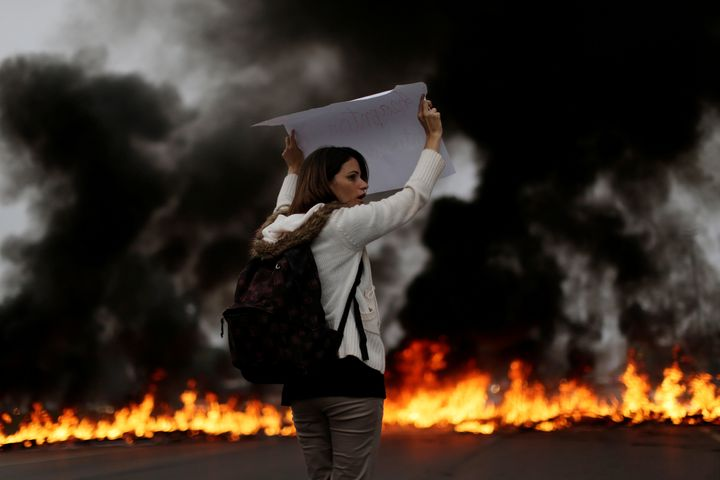 A demonstrators holds a placard in front of a burning barricade during a protest against President Michel Temer's proposal to