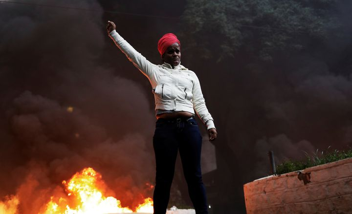 A member of Brazil's Movimento dos Sem-Teto (Roofless Movement) gestures in front of a burning barricade in Sao Paulo, Brazil